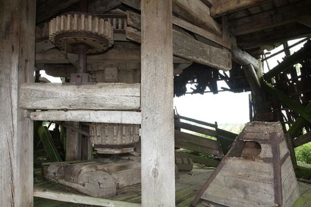 wind powered building: Wooden mechanism of an old abandoned windmill Stock Photo