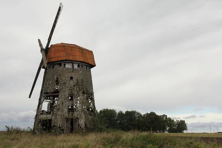 wind powered building: Old abandoned wooden windmill in the field