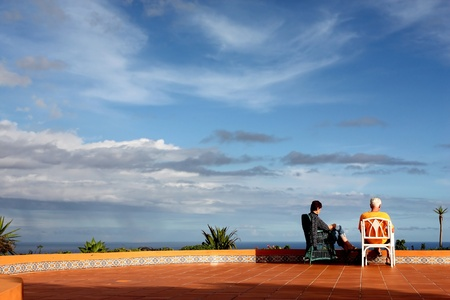 Madeira,Portugal,November 27,2010; A mature couple sitting on chairs reading and enjoying sea view