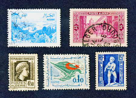Close up of five postally used cancelled Algerian stamps on black
