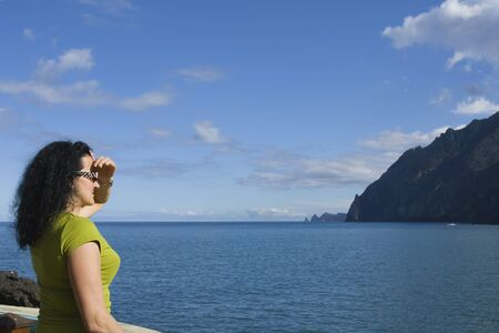 Youg single woman dressed in green t-shirt standing on a sea shore and watching horizon Stock Photo - 9319754