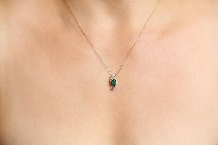 Gold necklace with a green stone pendant on females neck photo