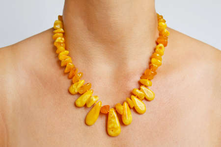 Yellow amber beads on a womans neck photo