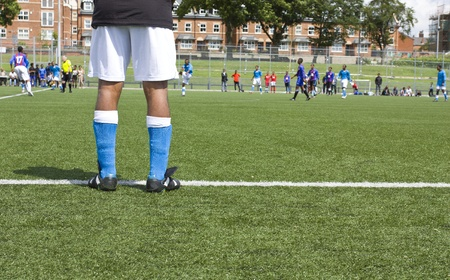 Rear view of substitute soccer player standing at the sideline of the field