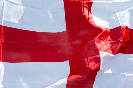 National flag of England red cross on white waving in the sky photo