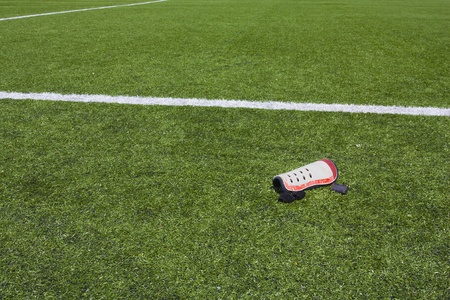 foreleg: Artificial grass field background with leg protection pad in the foreground Stock Photo