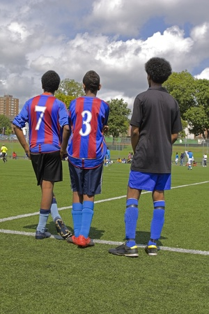 three soccer players watching the game on the pitch Editorial