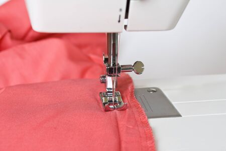 close up of red cloth on the sewing machine