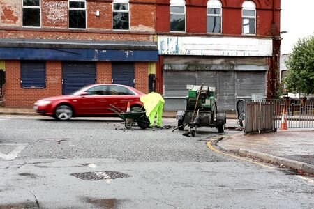Man in bright clothing doing road repair work on the street with traffic passing by Stock Photo - 10321761