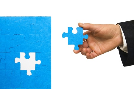 missing piece: Hand holding the last piece of a puzzle isolated on white background