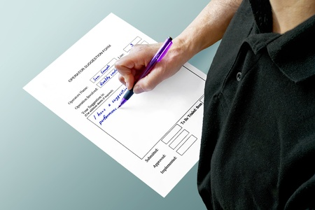 operative: upper body and hand holding a pen and filling in suggestion form