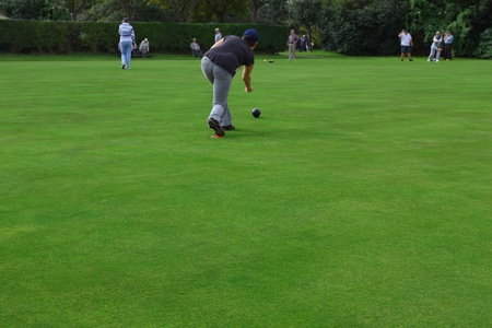Rear view of a woman on the bowling green throwing a bowl