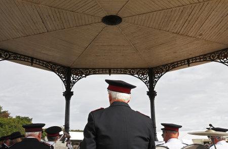 Brass band in uniform playing popular jazz music under gazebo outdoor in public