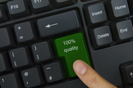 Close up of the finger on the green 100 % quality key of the keyboard Stock Photo