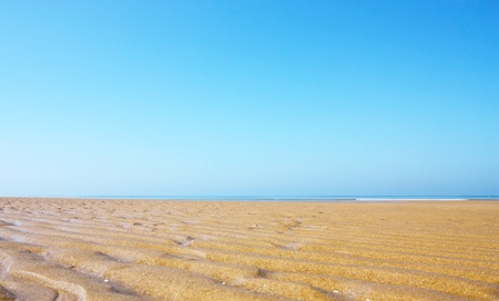 Wavy pattern of sand on the beach with blue sea, sky and horizon photo