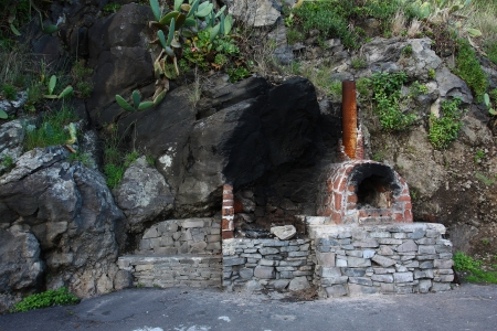 Old fashioned brick and stone fireplace by the steep rock in a tropical country