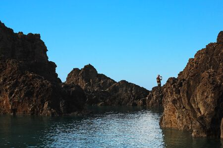 coastal erosion: Tourist taking picture of the beautiful landscape on the rocky path by the blue lagoon