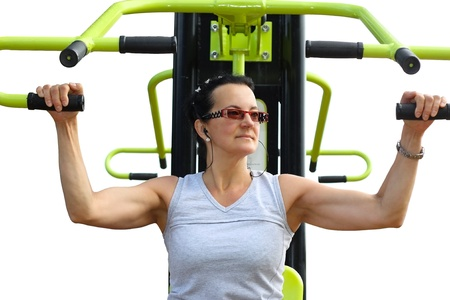 Young attractive woman with glasses exercising on a training machine isolated on white background photo