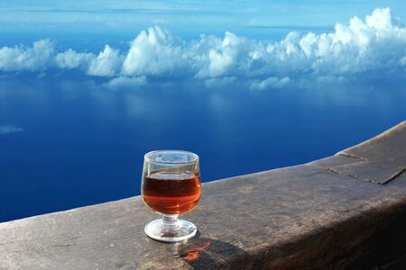 A glass of alcoholic drink on a wooden bar above the sea and clouds