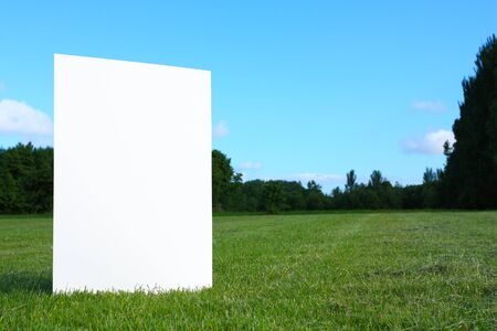 A big white empty billboard for advertising standing on the green grass in the field with trees  far away in a background and blue sky above