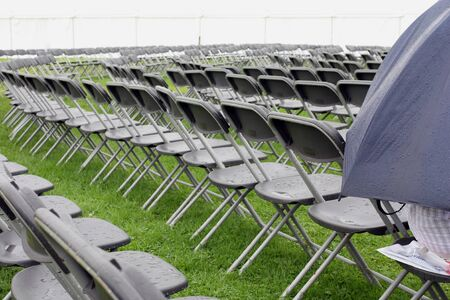 folding chair: Wet and empty rows of seats at a venue outdoors on a rainy day Stock Photo