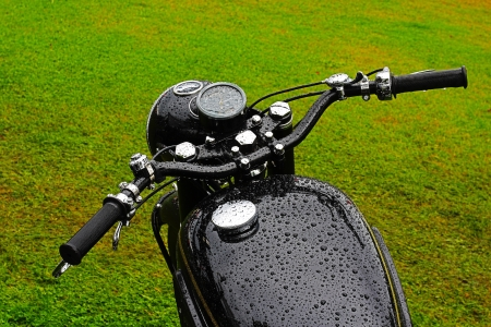 Bikers view  of an old black wet vintage motorcycle on the green grass