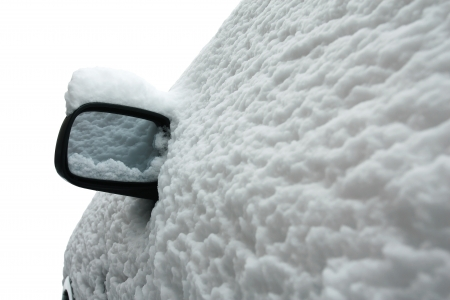 Side view of a car in winter after snow storm isolated on white background  The whole car is covered with snow