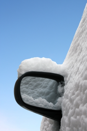 Winter, sunny day after storm  Car side mirror covered with snow isolated against blue sky Stock Photo