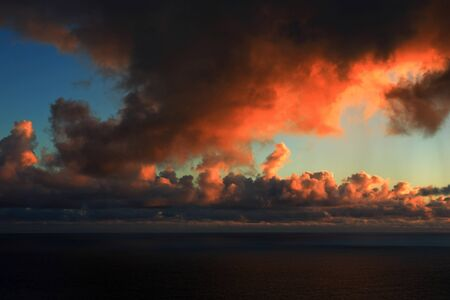 View from a hill top  Unusual cloud formation in the sky above the sea lit by sun  with dramatic colors Stok Fotoğraf