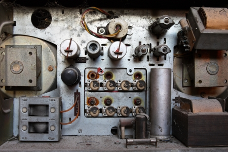 View of an open old dusty analog radio with very big parts of old technology