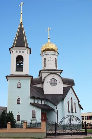 Christian orthodox church with golden cupolas against blue sky