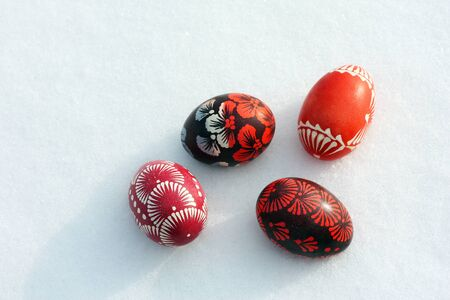 Top view of a few hand decorated easter eggs lying on the snow isolated Reklamní fotografie