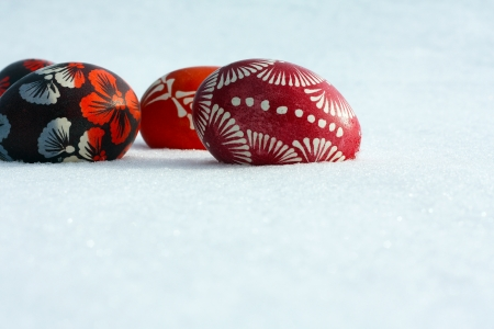 Low angle shot of a few hand painted easter eggs isolated lying on the snow with foreground copy space