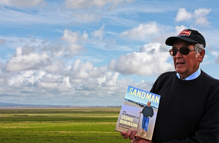 zoomed in: UNITED KINGDOM CIRCA JULY 2012 Mr Cedric Robinson MBE official UK Queen s Guide to the Sands and author of Sandman posing at Kents Bank station with his book  If zoomed in next to horizon one can see line of people actually crossing the Morecambe Bay Editorial