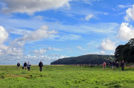 next horizon: UNITED KINGDOM MORECAMBE BAY NEAR KENT S BANK STATION CIRCA JULY 2012 Beautiful landscape with green grass blue sky and hilly forest People coming towards camera If zoomed in next to horizon  can see line of people still crossing the Morecambe Bay  Editorial