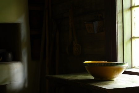 old times: A big handcrafted clay bowl on the table lit by light beam coming in from the window in the ancient mode kitchen shows lifestyle in 18 - 19 century Stock Photo