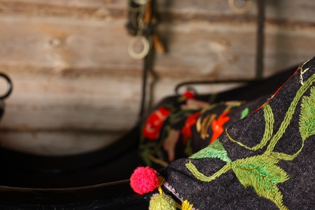 Close up of hand crafted embroidered horse carriage rug placed on a horse carriage in the stables