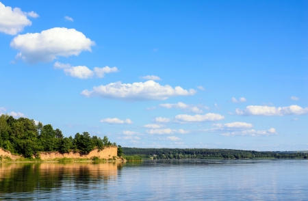 Tranquil scenery of a big calm lake river with steep yellow scarp on the shore, calm reflection, forest on the horizon and blue sky with a few white clouds in a nice order