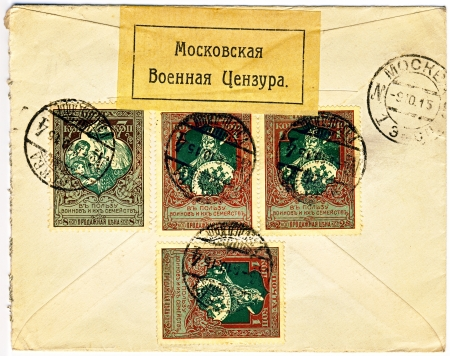 censor: Back of an old yellow WW1 world war one military censored envelope stamped in tsarist Russia, dated 9th of October 1915 with Moscow military censor label sticker and four postage stamps with old warrior depicted