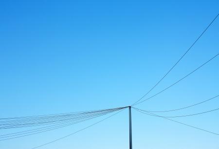 periferia: Palo di telefono e linee appesi rete contro il cielo blu