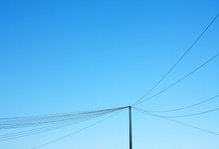 Telephone pole and hanging lines network against blue sky