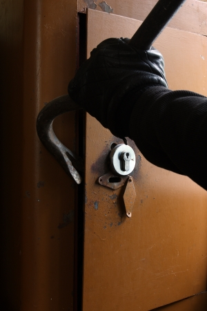 Burglar in black gloves breaking the safe with a crowbar Stock Photo