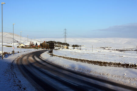 powerlines: View  of a snowy highway leading to the white hills  in winter