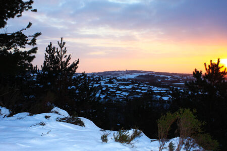 Winter sunset landscape of the snow covered hills of Pennines around Manchester with rooftops of Rochdale town in the distance