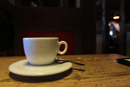 White cup, teaspoon and saucer on wooden table in the dark cafe Stok Fotoğraf