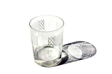 Decorated half full of water clear glass with shadow isolated on white background
