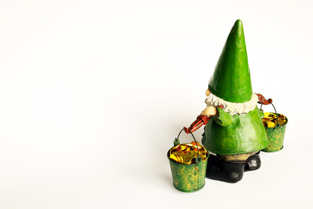 Top rear view of green gnome with big shoes, hat and white beard carrying buckets full of shiny gold coins isolated on grey gray white