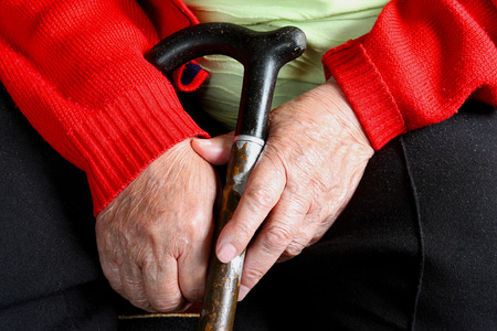 Elderly woman in red sweater sitting and holding her walking stick