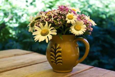 Daisies and other flowers in a decorated vintage clay jug on woden table outdoor with blurry summer foliage