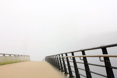 Modern empty bridge with wet metal railings in mist looks like going nowhere Stock Photo